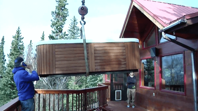 a Waterworks hot tub being lifted by a crane onto a porch in Alaska
