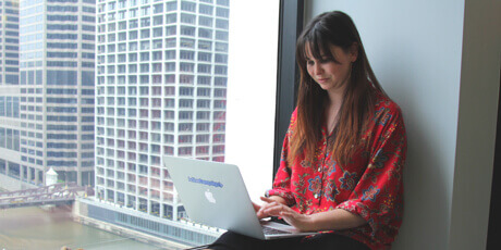 Woman working on her laptop in an office, seated next to a window that overlooks a river and tall buildings