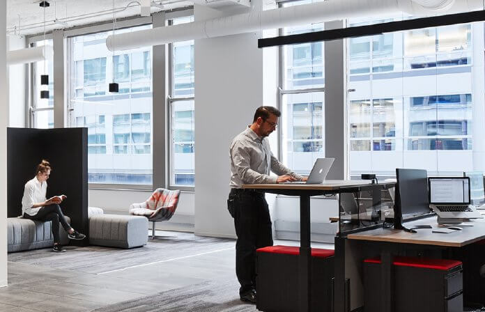 Man standing at desk, working on laptop