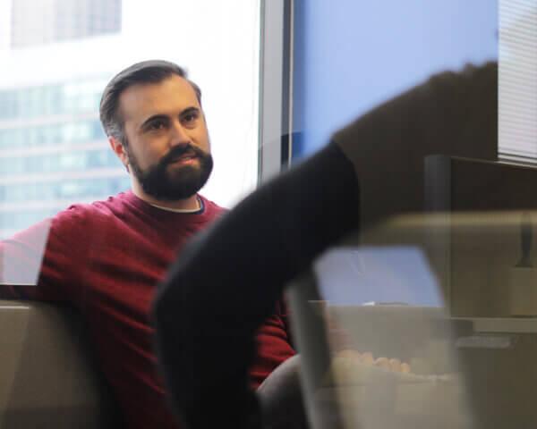 Man seated near window in office environment, listening