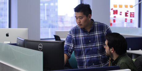 Two men in an office looking at large computer monitors together