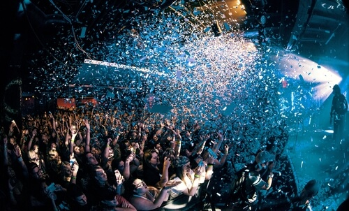 Picture of an audience getting confetti dumped on them